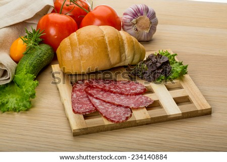 Salami sausages sliced with basil and bread - stock photo