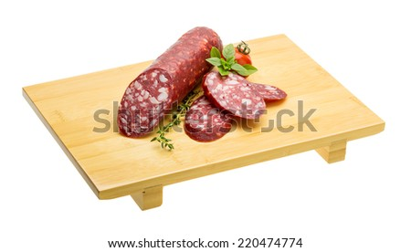 Salami sausages sliced with basil and tomato - stock photo