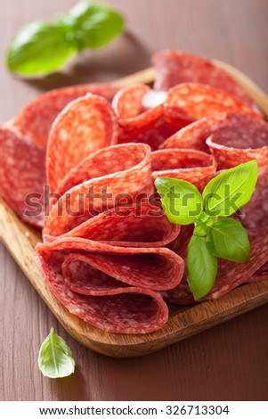 salami slices in wooden plate - stock photo