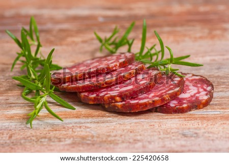 salami slices with pepper and rosemary on wooden background - stock photo
