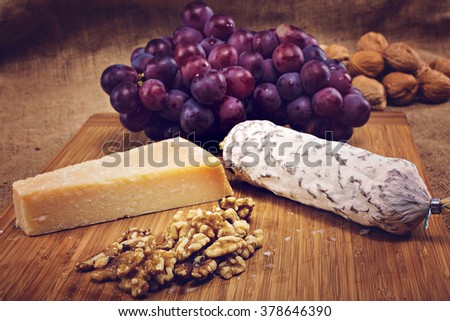 salami with nuts on a wooden platter with grapes