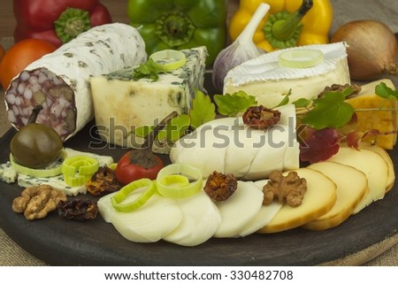 Salami with walnuts. Delicious specialty. Different kinds of cheese and vegetables. Healthy dairy products.  - stock photo