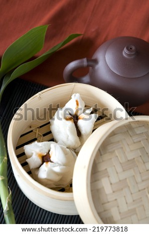 salapao in bamboo tray with tea pot on red background - stock photo