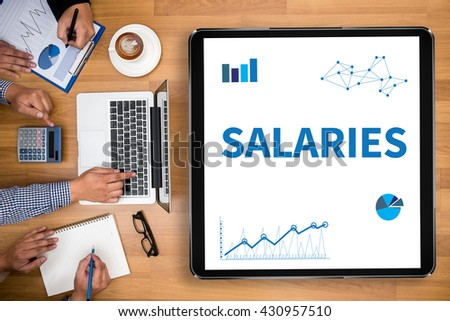 SALARIES Business team hands at work with financial reports and a laptop - stock photo