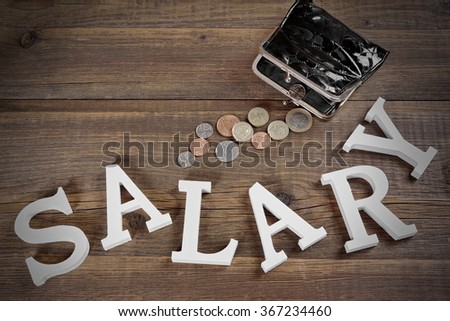Salary Sign Made From White Wood Letter And Empty Black Purse With Different British Coins On The Rough Wood Background, Top View, Conceptual Image - stock photo