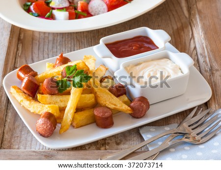 Salchipapas is a fast food dish from Latin America, sold in the streets of Lima, Peru and Colombia, Bolivia and Ecuador. - stock photo