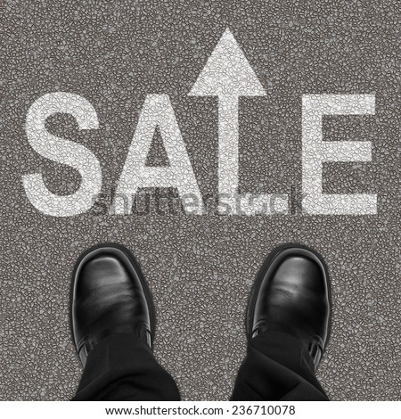 Sale ahead concept with business man feet on asphalt road with text and arrow - stock photo