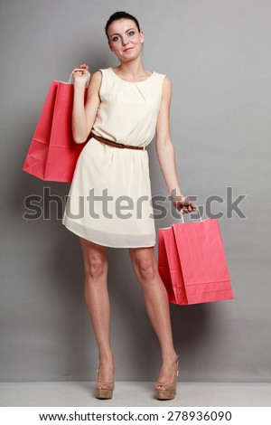 Sale and retail. Young woman girl with red shopping bags in hands on grey background in studio. - stock photo