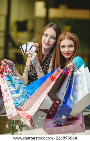sale and tourism, happy people concept - beautiful women with shopping bags and credit card in the ctiy