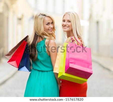 sale and tourism, happy people concept - beautiful women with shopping bags in the ctiy - stock photo