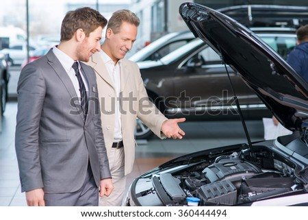 Sale assistant showing the car  - stock photo