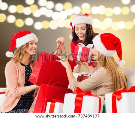 sale, christmas, holidays and people concept - smiling women in santa helper hats with shopping bags and many gift boxes over lights background