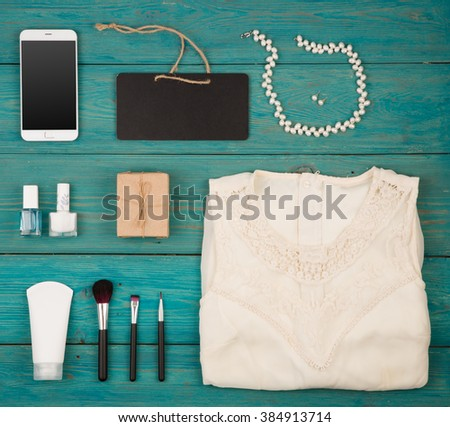 Sale concept - set of woman stuff on blue wooden background, essentials, accessories and cosmetics - stock photo