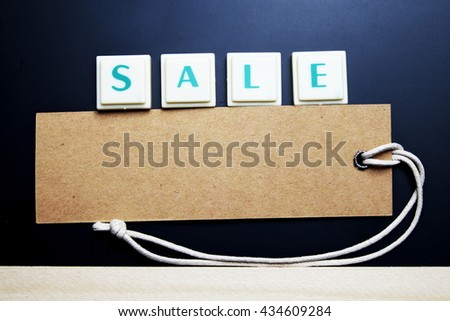 Sale concept. The words spelled by letters with sale tag, brown label on blackboard with wooden border. Dark tone. - stock photo