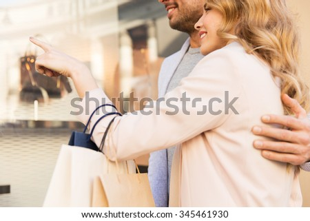 sale, consumerism and people concept - close up of happy couple with shopping bags looking at shop window in city - stock photo