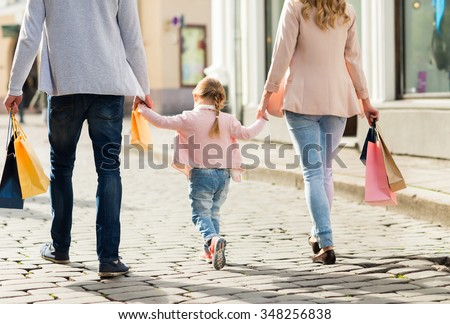 sale, consumerism and people concept - close up of happy family with little child and shopping bags in city - stock photo