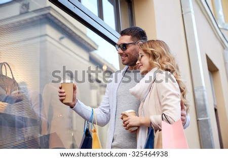 sale, consumerism and people concept - happy couple with shopping bags and coffee paper cups looking at shop window in city - stock photo