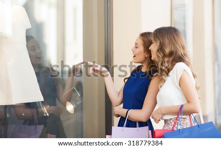 sale, consumerism and people concept - happy surprised young women with shopping bags pointing finger to shop window outdoors - stock photo