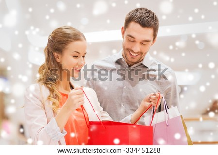 sale, consumerism and people concept - happy young couple showing content of shopping bags in mall with snow effect - stock photo