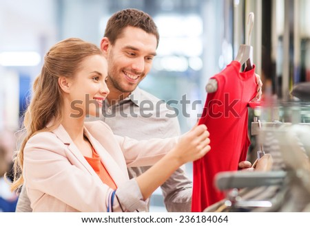 sale, consumerism and people concept - happy young couple with shopping bags choosing dress in mall - stock photo