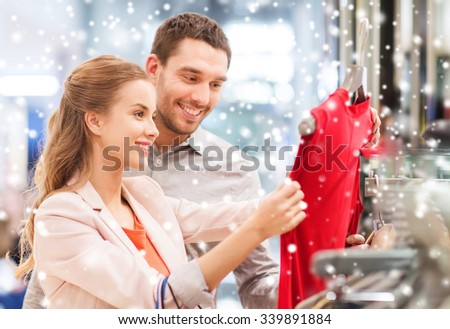 sale, consumerism and people concept - happy young couple with shopping bags choosing dress in mall with snow effect - stock photo