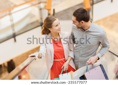 sale, consumerism and people concept - happy young couple with shopping bags rising on escalator and talking in mall