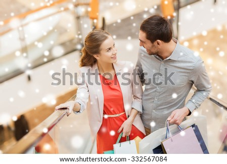 sale, consumerism and people concept - happy young couple with shopping bags rising on escalator and talking and raising on escalator in mall with snow effect - stock photo