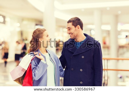 sale, consumerism and people concept - happy young couple with shopping bags talking in mall