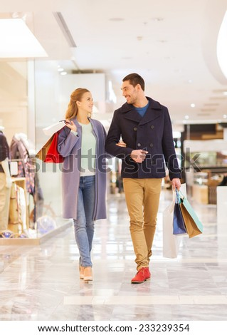 sale, consumerism and people concept - happy young couple with shopping bags walking and talking in mall - stock photo