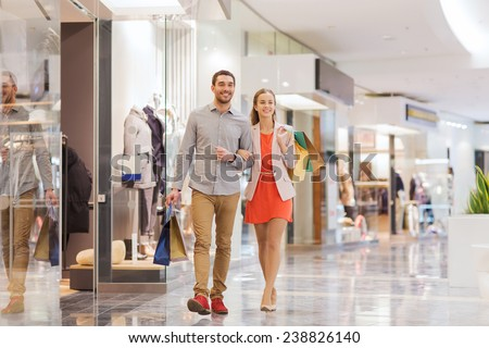 sale, consumerism and people concept - happy young couple with shopping bags walking in mall - stock photo