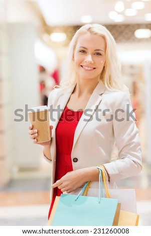 sale, consumerism and people concept - happy young woman with shopping bags and coffee paper cup in mall - stock photo
