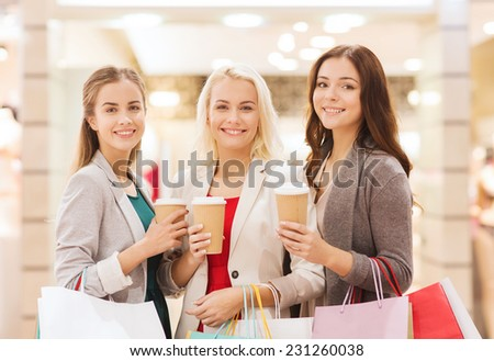 sale, consumerism and people concept - happy young women with shopping bags and coffee paper cup in mall - stock photo