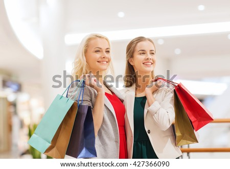 sale, consumerism and people concept - happy young women with shopping bags in mall - stock photo