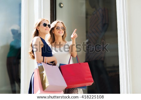 sale, consumerism and people concept - happy young women with shopping bags pointing finger outdoors - stock photo