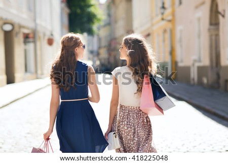 sale, consumerism and people concept - happy young women with shopping bags walking along city street - stock photo