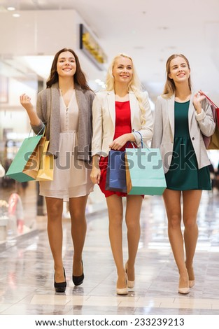sale, consumerism and people concept - happy young women with shopping bags walking in mall