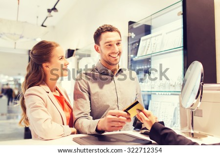 sale, consumerism, shopping and people concept - happy couple with credit card at jewelry store in mall - stock photo