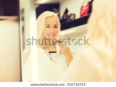 sale, consumerism, shopping and people concept - happy young woman choosing clothes and looking to mirror in mall - stock photo