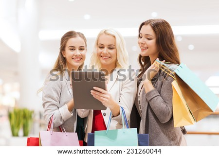 sale, consumerism, technology and people concept - happy young women with tablet pc and shopping bags in mall - stock photo