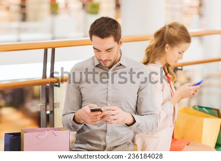 sale, consumerism, technology and people concept - young couple with shopping bags and smartphones in mall - stock photo