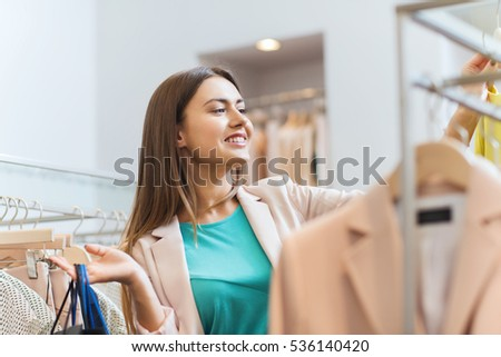 sale, fashion, consumerism and people concept - happy young woman with shopping bags choosing clothes in mall or clothing store
