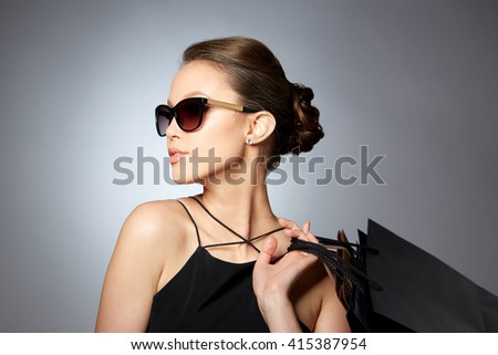 sale, fashion, people and luxury concept - happy beautiful young woman in black sunglasses with shopping bags over gray background - stock photo