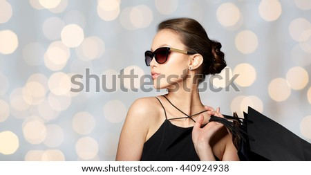 sale, fashion, people and luxury concept - happy beautiful young woman in black sunglasses with shopping bags over holidays lights background - stock photo