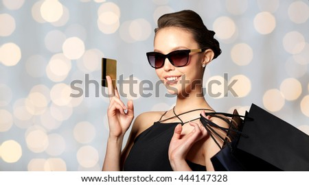sale, finances, fashion, people and luxury concept - happy beautiful young woman in black sunglasses with credit card and shopping bags over holidays lights background - stock photo