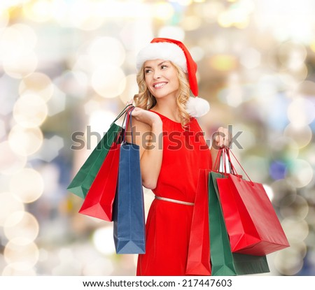 sale, gifts, christmas, holidays and people concept - smiling woman in red dress and santa helper hat with shopping bags over lights background