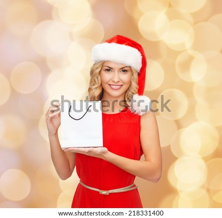 sale, gifts, christmas, holidays and people concept - smiling woman in red dress and santa helper hat with white blank shopping bag over beige lights background - stock photo