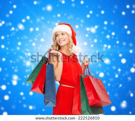sale, gifts, christmas, holidays and people concept - smiling woman in red dress and santa helper hat with shopping bags over blue snowing background - stock photo