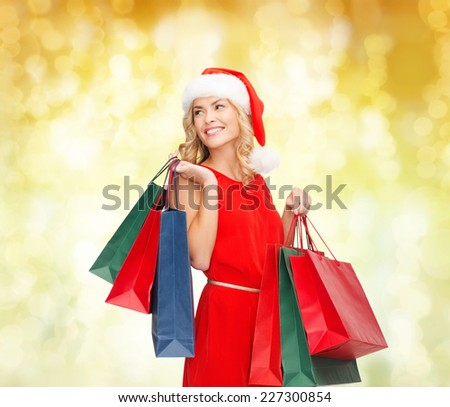 sale, gifts, christmas, holidays and people concept - smiling woman in red dress and santa helper hat with shopping bags over yellow lights background - stock photo