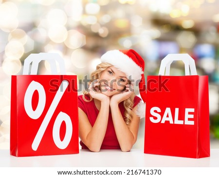 sale, gifts, christmas, holidays and people concept - smiling woman in santa helper hat with shopping bags and percent sign over lights background - stock photo
