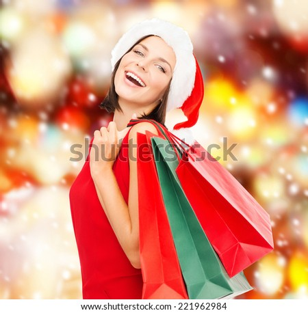 sale, gifts, christmas, xmas concept - smiling woman in red dress and santa helper hat with shopping bags - stock photo